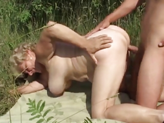 german granny outdoor with youthful guy by troc