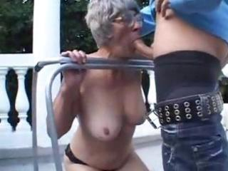 granny is outside engulfing on a younger ramrod